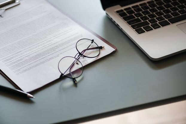 Contract with glasses and a laptop on a grey desk-min