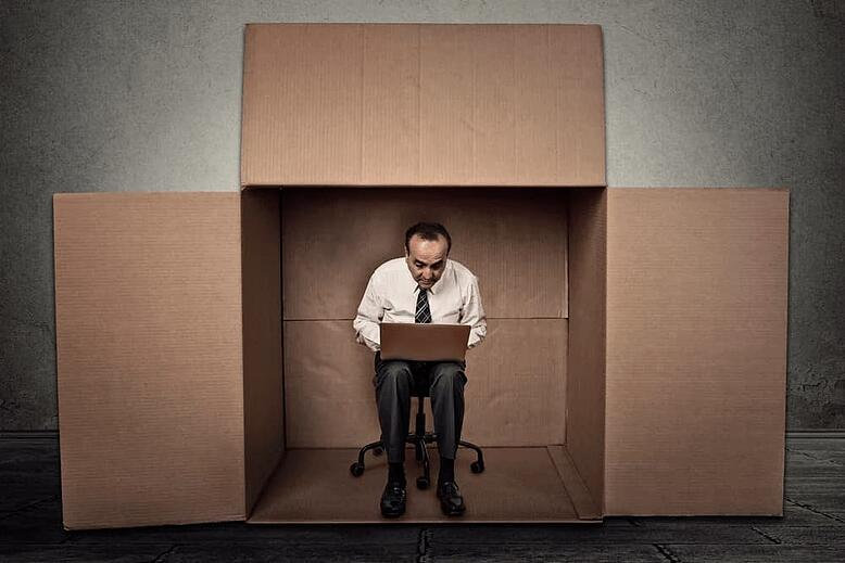 Man huddled over a laptop sitting within a cardboard box-min
