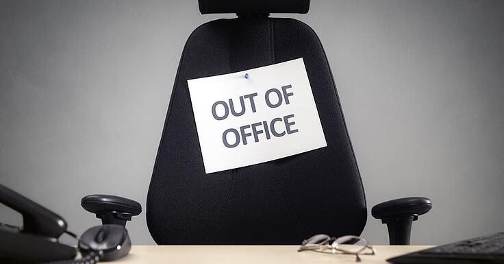 Out of office sign pinned to a black office chair-min