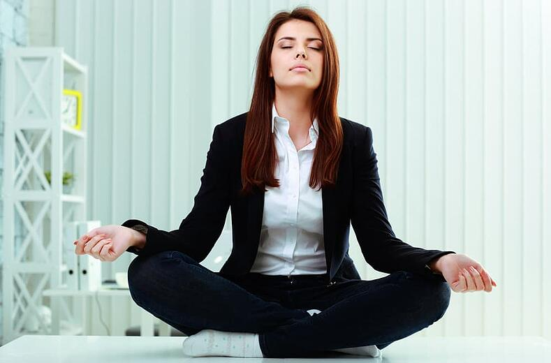 Young beautiful businesswoman meditates on the table in office-min