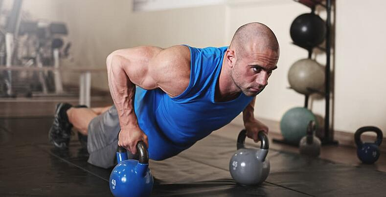 bodybuilder working out and doing push ups at the gym-min