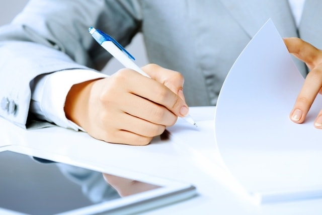 Close up image of businesswoman hands signing documents-min