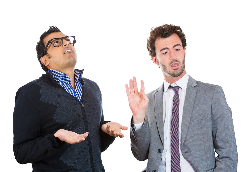 Closeup portrait, annoyed nerd man with black glasses by what a business guy in suit is telling him, talk to hand, isolated white background. Negative human emotion facial expression feelings.-min
