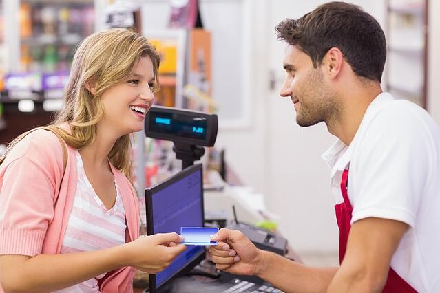 Log your expenses with Breathe. Smiling woman at cash register paying with credit card in supermarket
