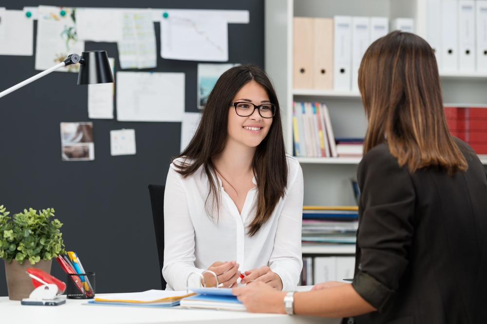 Performance meeting between two women in an office