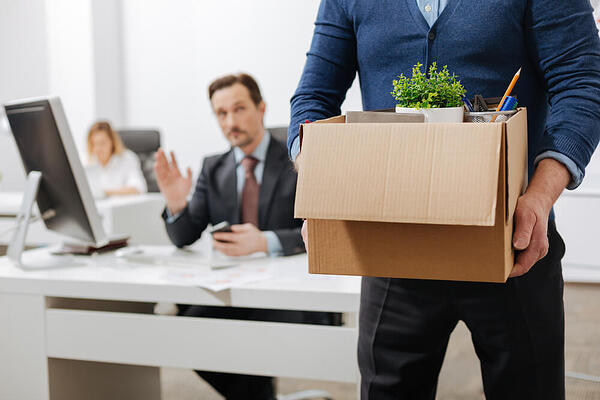 Employee leaving office with his box of belongings