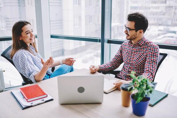 millennial employees desk worker laptop talking office