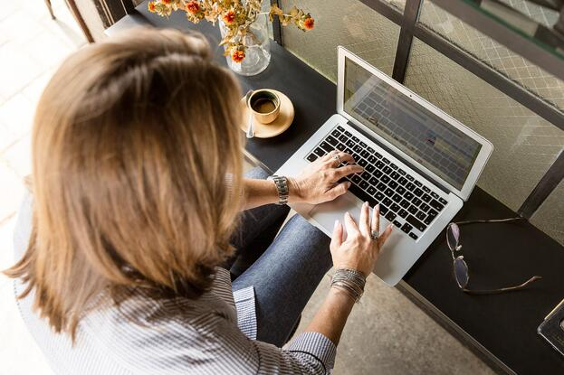 Lady sitting at a table on her laptop