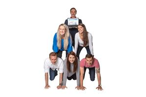 Breathe employees kneeling in a human pyramid while holding a laptop