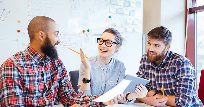 three happy people chatting in an office