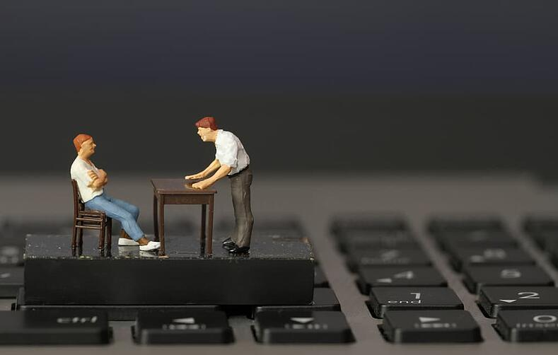 working online concept-miniature businessman boss angry with employee on laptop computer-min