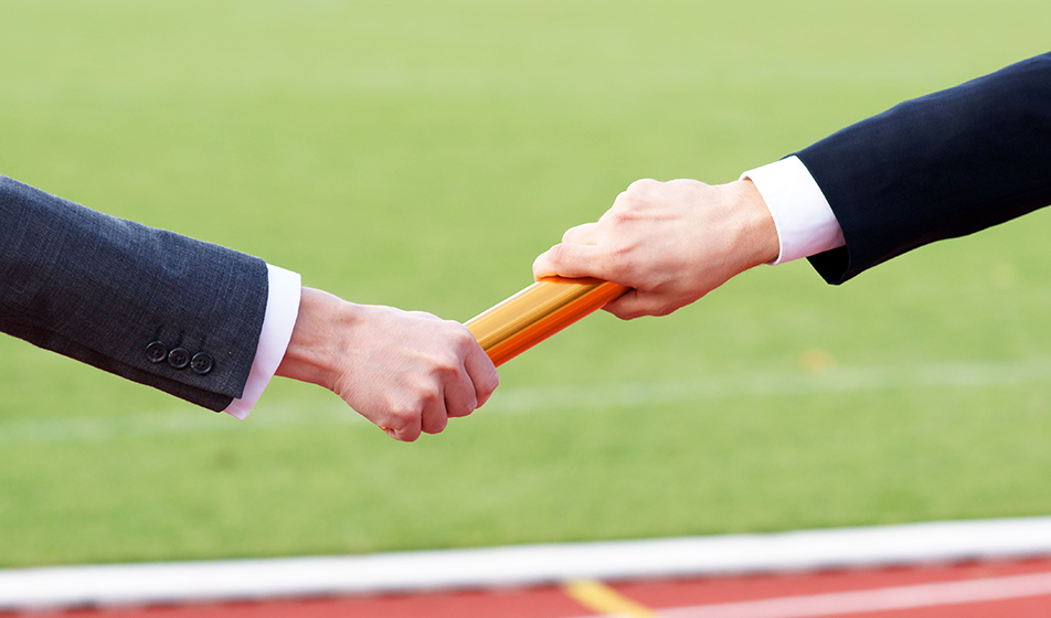 Business men changing baton in a relay race