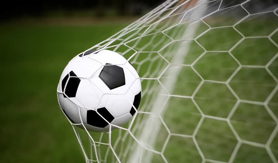 Black and white football hitting the back of a net