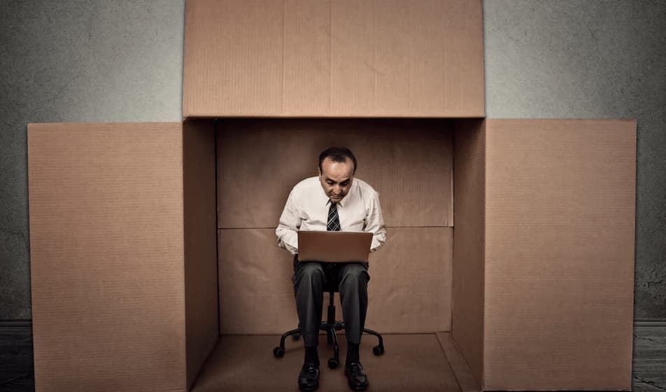 Man huddled over a laptop sitting within a cardboard box
