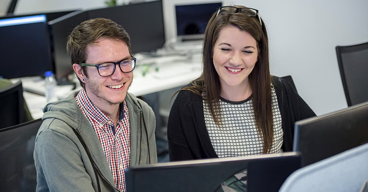 Happy employees looking at a computer screen