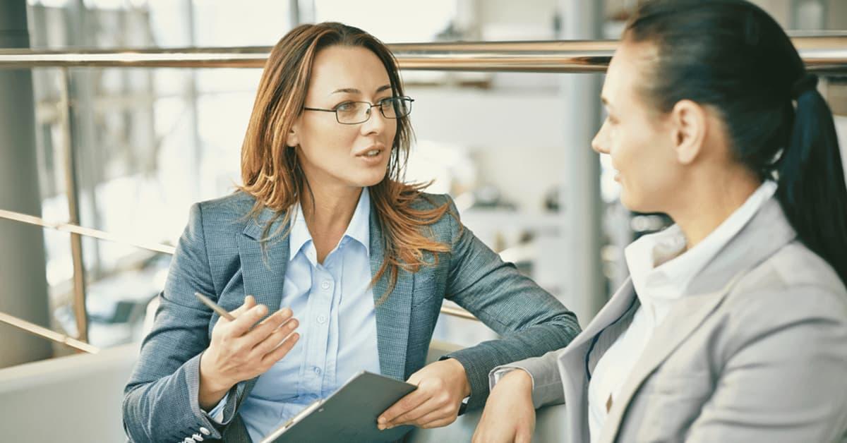Two women sitting down talking at work