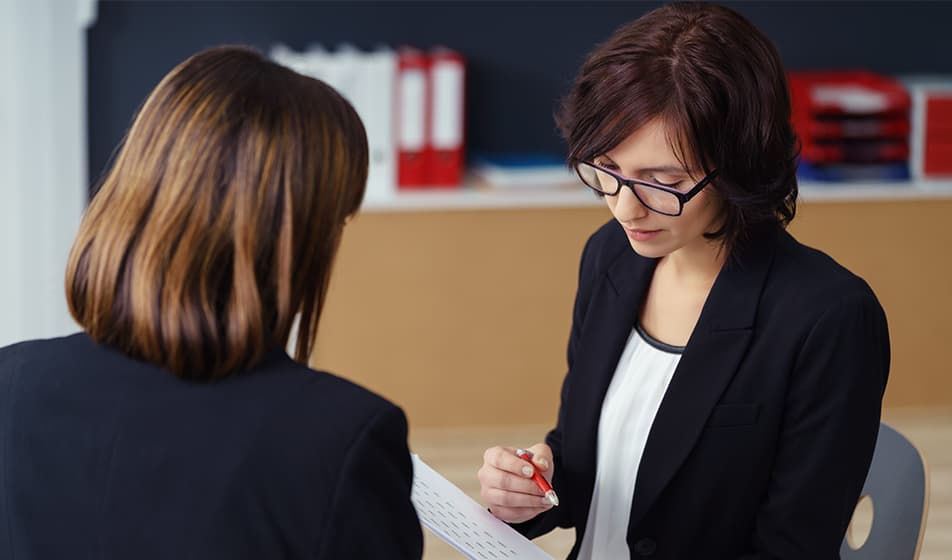 two suited women looking at a document