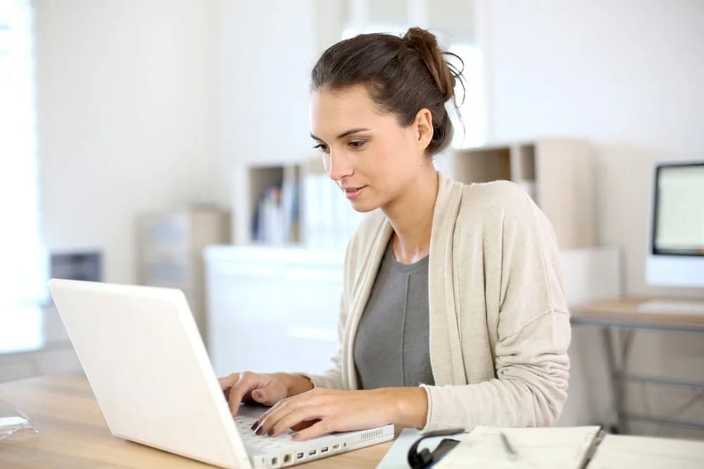 Lady sitting at her desk working on her laptop