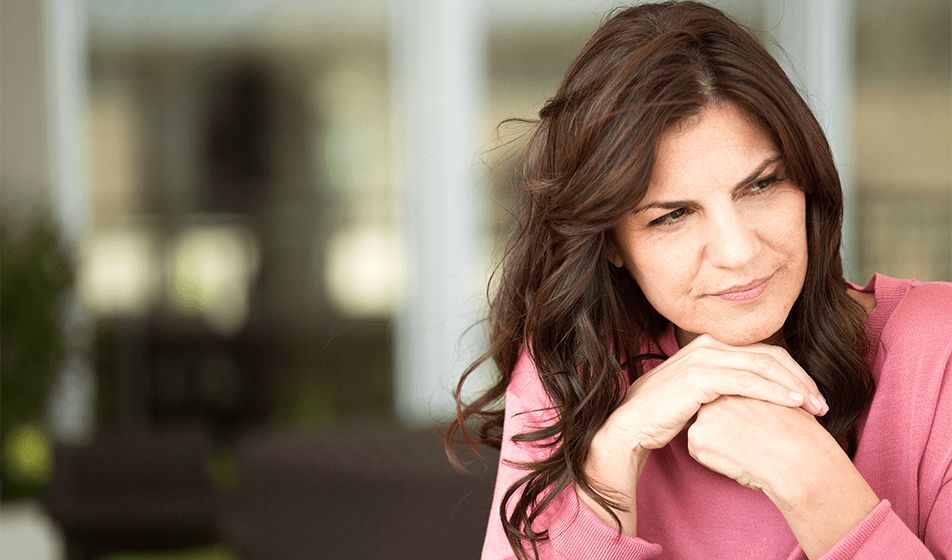 A woman looks serious as her hands are clasped under her chin