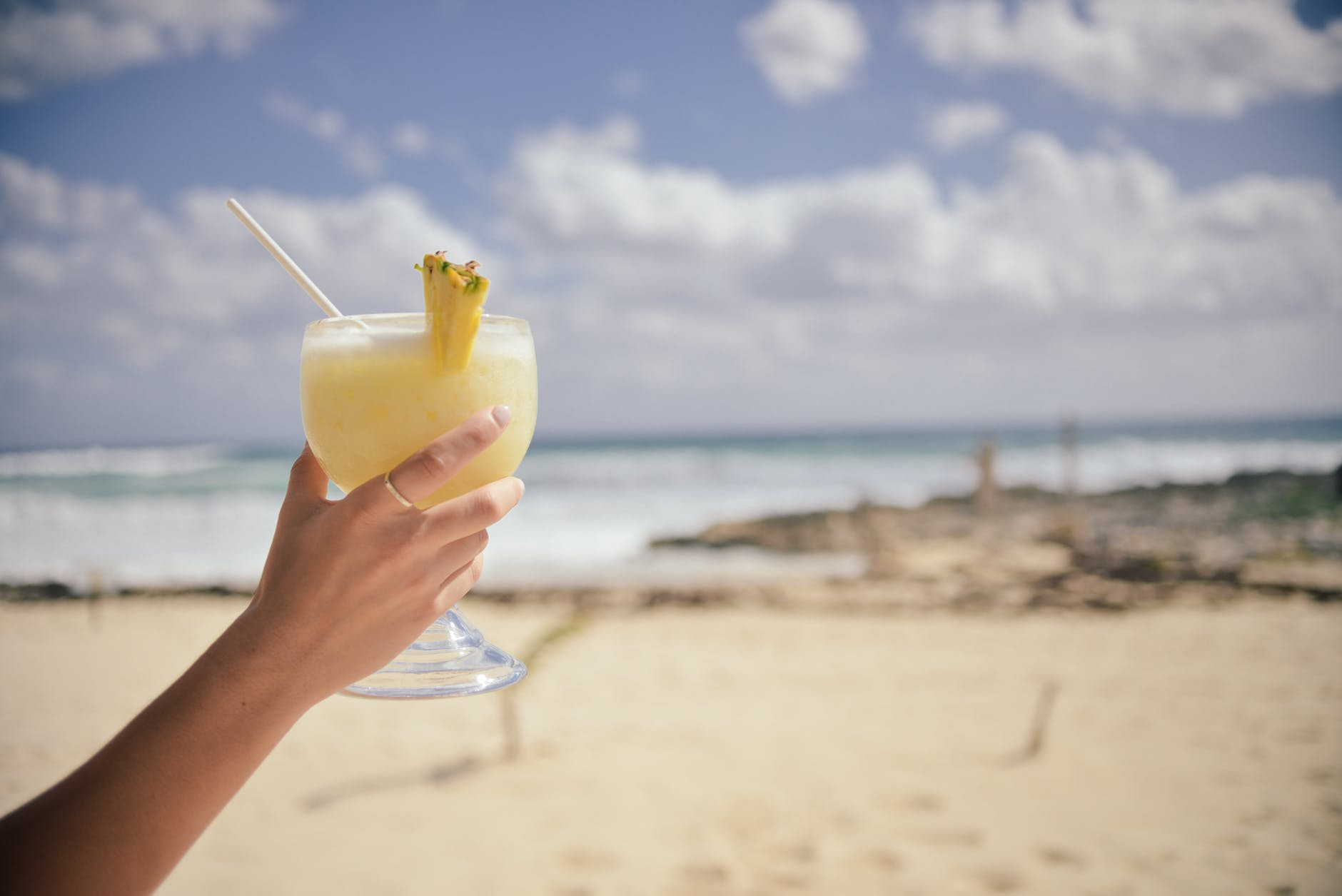 Lady holding a cocktail with a sandy beach in the background