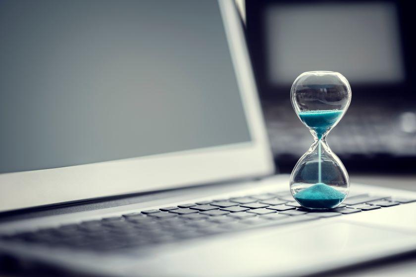 A sand timer sits on a laptop